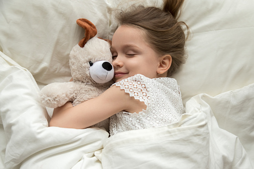 Cute little kid girl hugging teddy bear sleeping in bed