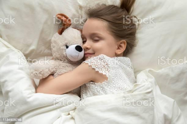 Cute little kid girl hugging teddy bear sleeping in bed picture id1134909746?b=1&k=6&m=1134909746&s=612x612&h=srf uqhhxoigwni3nj0xrjtm4jw2tyik 6vzpcm twk=