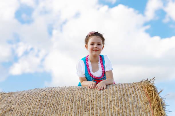 niedliche kleine kind mädchen in bayerischer tracht im weizenfeld auf heuhaufen - sommerfest kindergarten stock-fotos und bilder