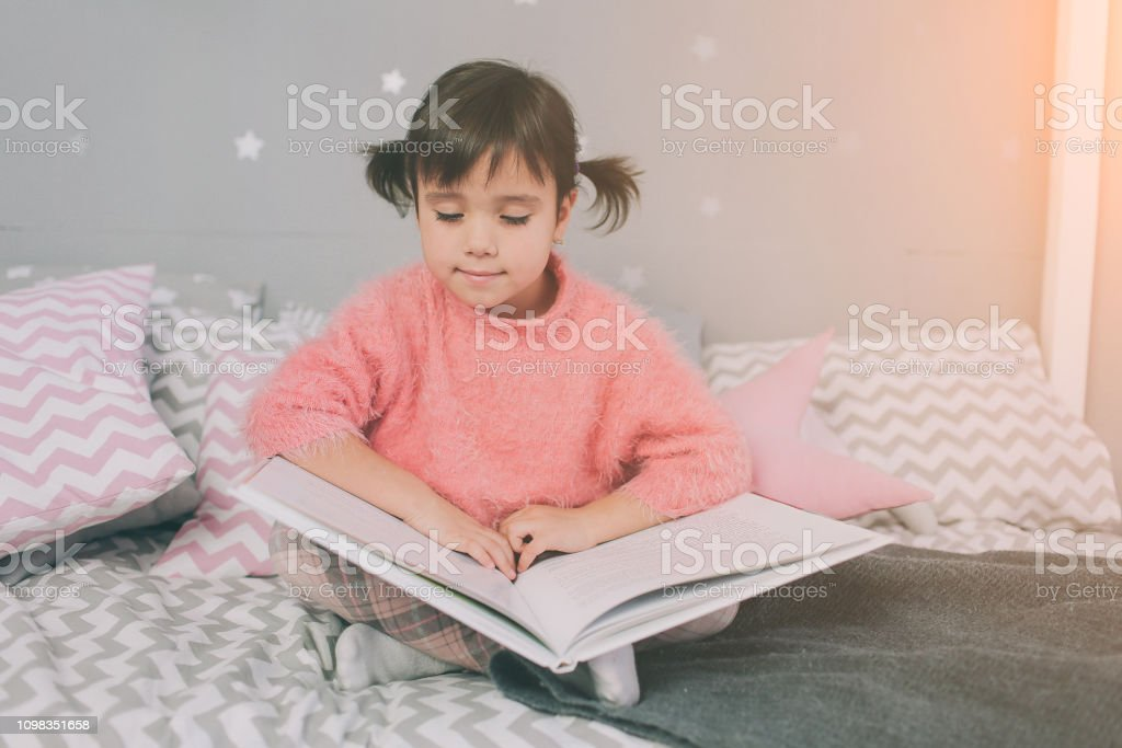 Cute little kid girl is reading a book at home. Funny lovely child...