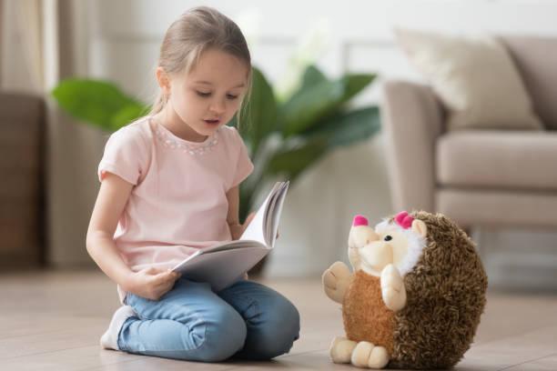 cute little kid girl playing alone reading book to toy - reading zdjęcia i obrazy z banku zdjęć