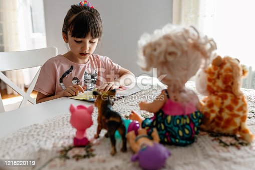 Cute little kid girl playing alone reading book to toys