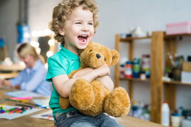 süße kleine kind umarmt teddybär - teddybär stock-fotos und bilder