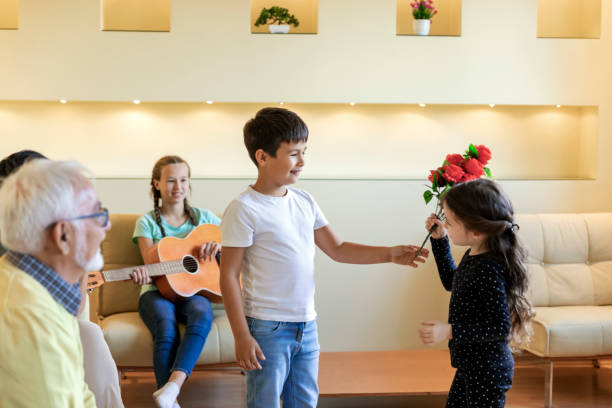 Cute Little Kid is Giving a Bouquet of Red Roses to his Young Sister. Cheerful Multi-Generation Family is Spending the Time Together in Comfortable Apartment. Young Girl is Receiving Flowers as a Birthday Present from her Brother. group of friends giving gifts to the birthday girl stock pictures, royalty-free photos & images