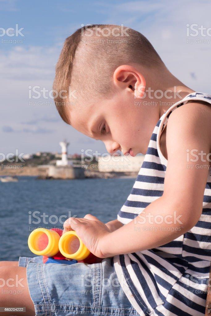 바다와 등 대의 배경에 쌍안경을가지고 노는 귀여운 아이 royalty-free 스톡 사진