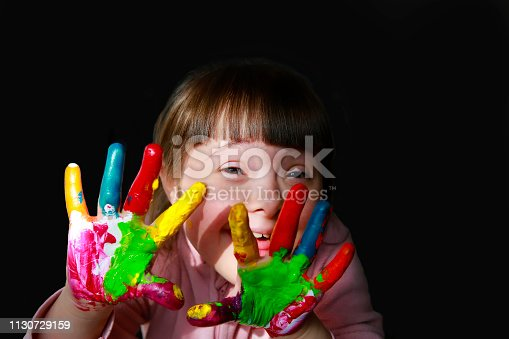 istock Cute little kid with painted hands isolated on the black 1130729159