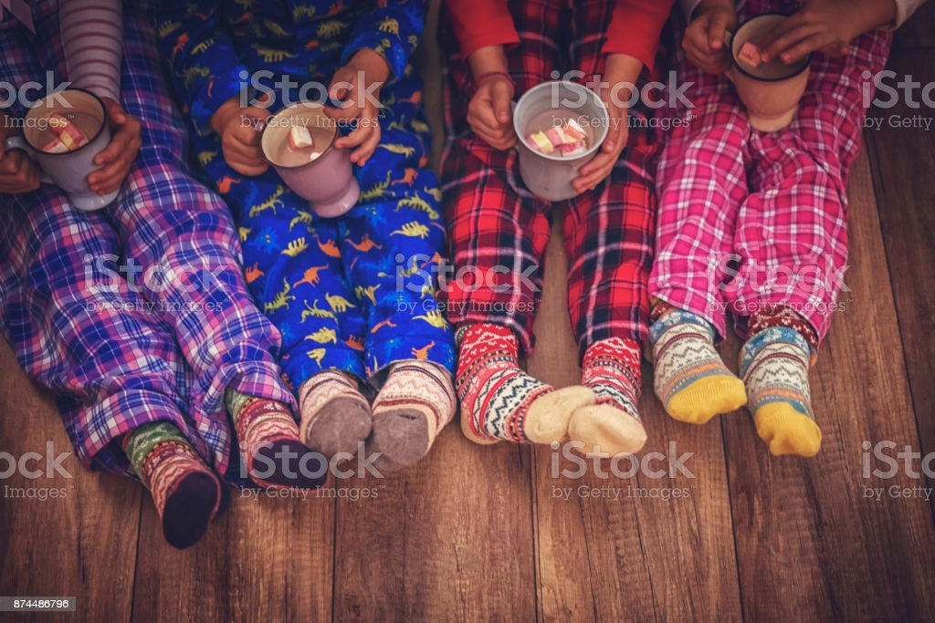 Cute Little Kids in Pyjamas and Christmas Socks Drinking Hot Chocolate with Marshmallows for Christmas stock photo