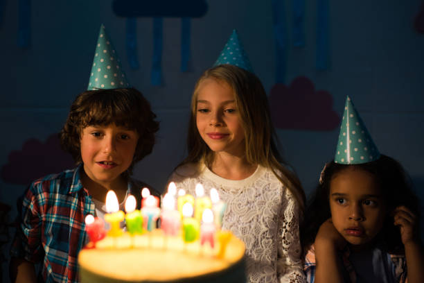 Cute Little Kids Looking At Birthday Cake With Burning Candles In Dark Room Stock Photo