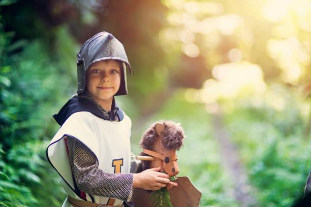 niedliche kleine ritter fütterung sein pferd im wald - kleine jungen kostüme stock-fotos und bilder