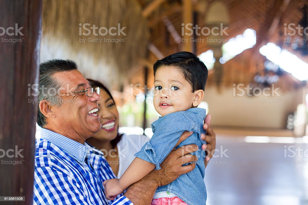Cute little latin boy being held by grandparents - foto de stock