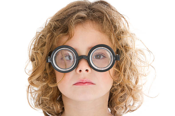 Cute little nerd squinting Adorable 6 years-old little girl needing glasses nerd hairstyles for girls stock pictures, royalty-free photos & images