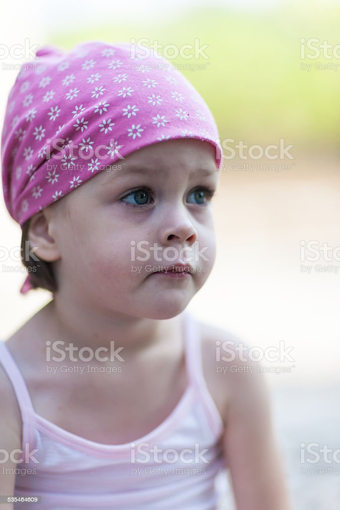 Cute little pensive girl looking for someone or something stock photo