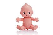 空の背景に座っている青い目のかわいいプラスチック製の赤ちゃん人形