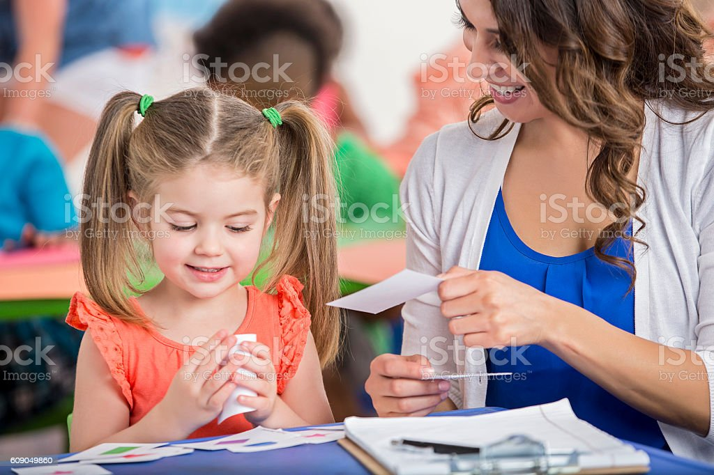 Cute little preschool girl working on flashcards with teacher stock photo