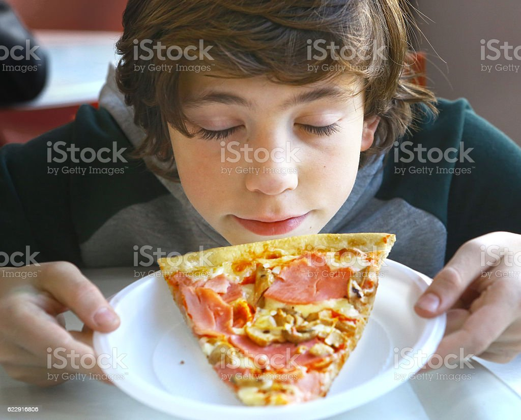 cute little preteen boy smelling pizza stock photo