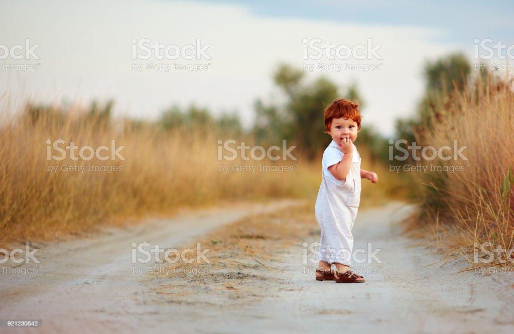 ruiva bebê menino bonitinho andar no caminho rural, no dia de verão - foto de acervo