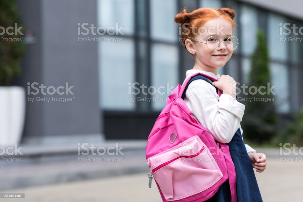 cute little redhead schoolgirl in eyeglasses holding backpack and smiling at camera stock photo