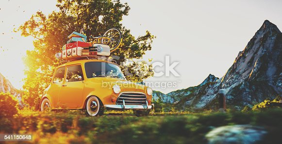 istock Cute little retro car goes by countryside road at sunset 541150648