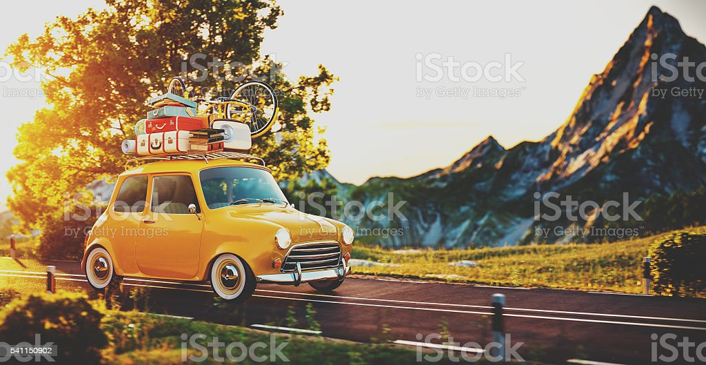 Cute little retro car goes by countryside road at sunset foto