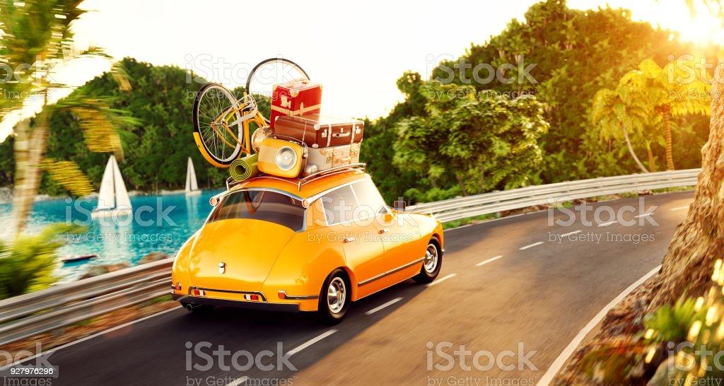 Niedliches kleine Retro-Auto mit Koffern und Fahrrad an der Spitze geht durch die Straße entlang schönen Hafen zwischen Berg am Sommertag. – Foto