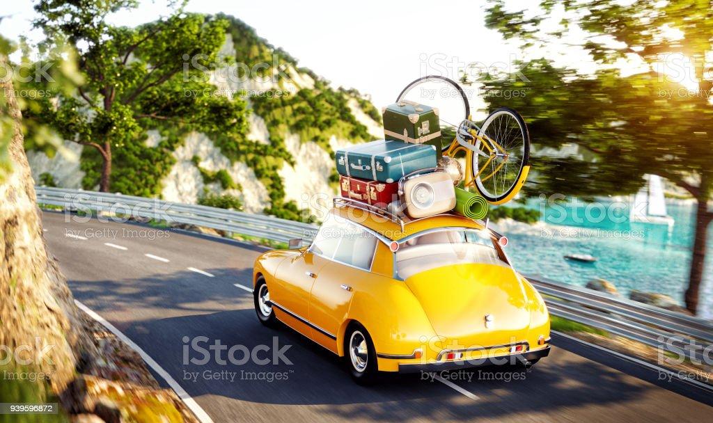 Niedliches kleine Retro-Auto mit Koffern und Fahrrad an der Spitze geht durch die Straße entlang schönen Hafen zwischen den Bergen im Sommertag. – Foto