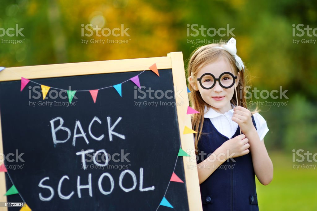 Cute little schoolgirl feeling excited about going back to school stock photo
