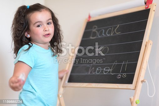 istock Cute little schoolgirl with chalkboard with text back to school. 1159885224