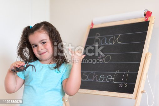 istock Cute little schoolgirl with chalkboard with text back to school. 1159885929