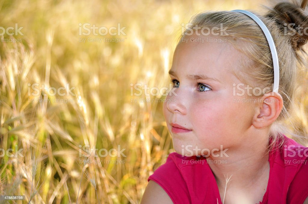 Cute little serious girl looking for someone or something stock photo
