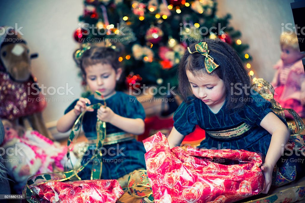 cute little sister girls unwrapping their gifts by christmas tree royalty free stock photo
