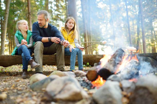 Nette kleine Schwestern und ihr Vater rösten Marshmallows auf Stöcken am Lagerfeuer. Kinder, die Spaß am Lagerfeuer haben. Camping mit Kindern im Herbstwald. – Foto