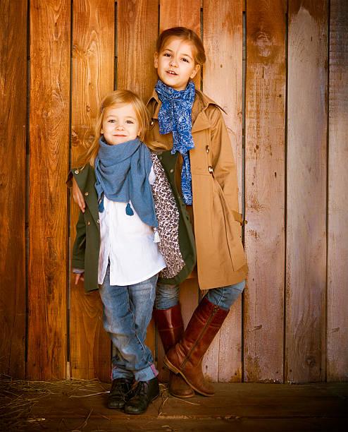 cute little sisters wearing autumn  clothes - kinder winterstiefel stock-fotos und bilder