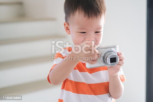 Cute little smiling Asian 2 - 3 years old toddler boy child taking photo using digital camera, Happy Kid using real camera to take a photo