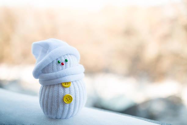 süße kleine schneemann auf dem hintergrund verschwommen - kindermütze häkeln stock-fotos und bilder