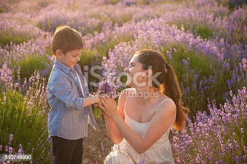 istock cute little son give bouquet of flowers to his happy beautiful mother 840749990
