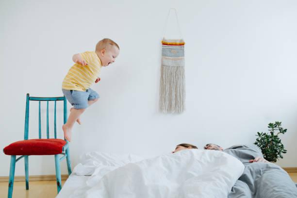 可愛的小兒子試圖喚醒他的父母。 - 惡意 個照片及圖片檔
