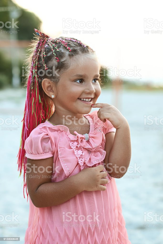 Cute little tanned girl with colored braids hairdo wearing a pink dress is very curious at the summer beach stock photo