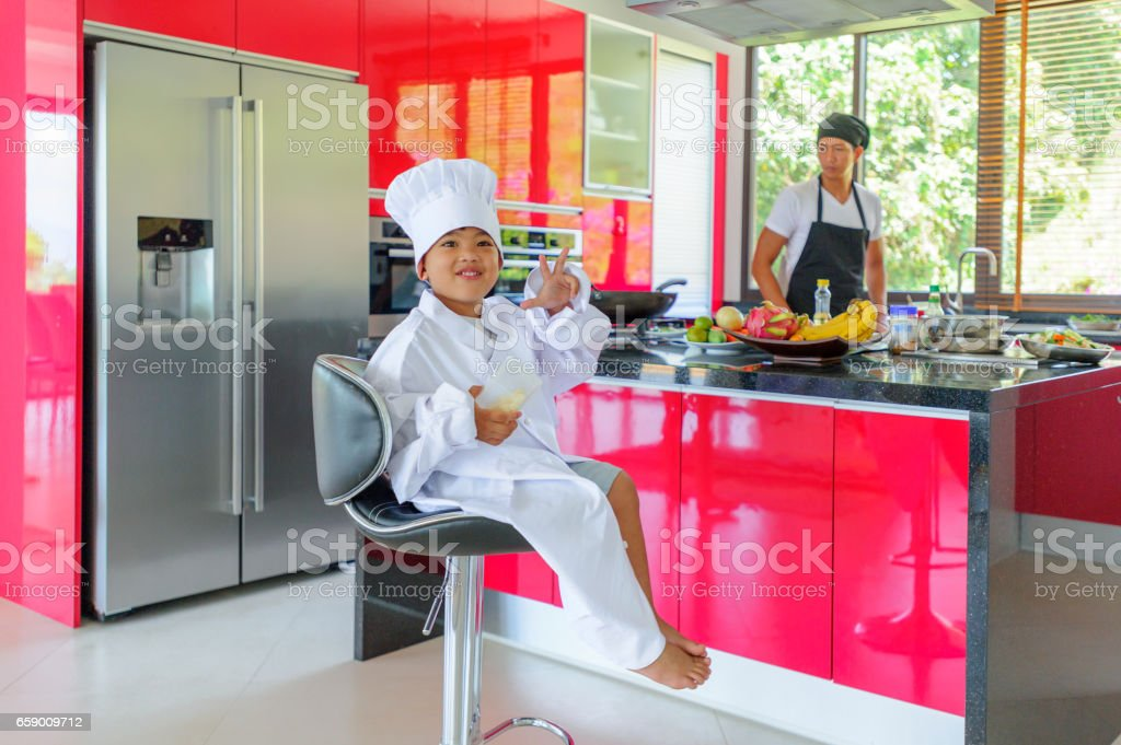 Cute little Thai boy in chef's hat and tunic sitting on a high chair in a modern style home kitchen. Dad is behind him making Thai food royalty-free stock photo
