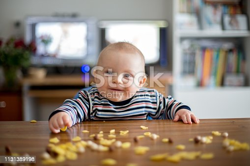 istock Cute little toddler boy eating cornflakes and smiling 1131389198