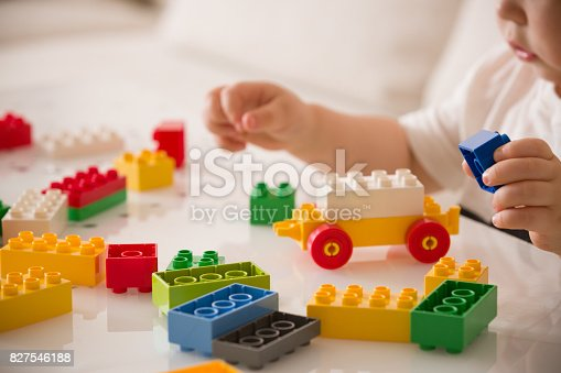 istock Cute little toddler boy playing colorful plastic blocks on the sofa indoors. child having fun and building out of bright constructor bricks. Early learning. Creative. 827546188