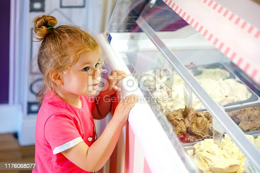 Cute little toddler girl choosing and buying ice cream in a cafe. Happy baby child looking at different sorts of icecream. Sweet home made dessert.