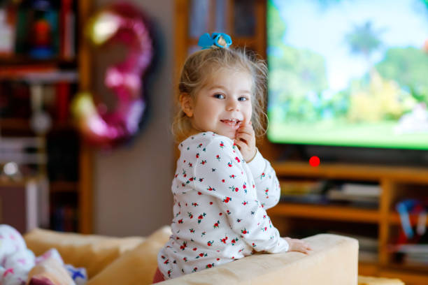 Nettes kleines Kleinkind Mädchen in Nachtwäsche Pyjamas cartoons oder Film im Fernsehen. Glücklich gesundes Baby Kind zu Hause. – Foto