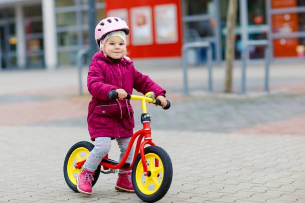 Nettes kleines Kleinkind Mädchen in Schutzhelm reiten auf Lauf-Balance-Bike. Glücklich gesunde semliche Kinder mit Spaß beim Lernen auf schlankere Fahrrad. Aktives Kind an kalten Tagen im Freien. – Foto