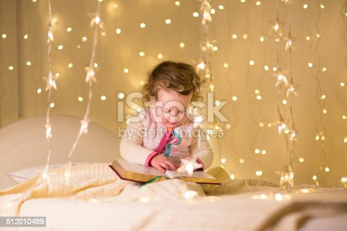 istock Cute little toddler girl reading book in Christmas lights 512010489