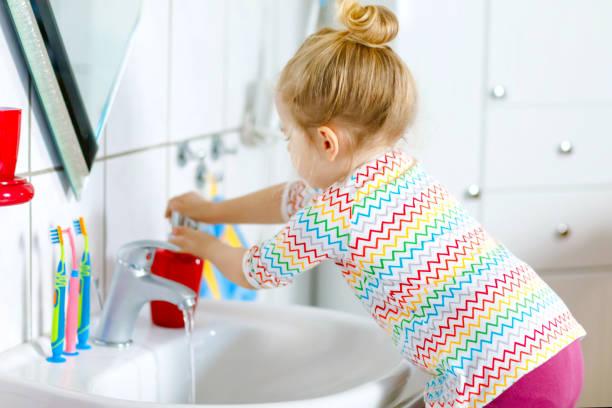 Nettes kleines Kleinkind Mädchen waschen Hände mit Seife und Wasser im Bad. Entzückende Kind lernen Reinigung Körperteile. Hygiene-Routine-Aktion während der viralen Desease. Kind zu Hause oder im Kindergarten. – Foto