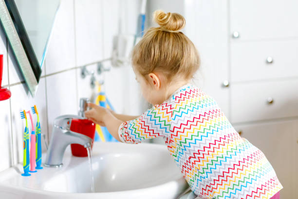 Cute little toddler girl washing hands with soap and water in bathroom. Adorable child learning cleaning body parts. Hygiene routine action during viral desease. kid at home or nursery. stock photo