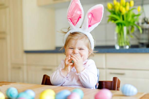 Niedliche kleine Kleinkind Mädchen Ostern Hasenohren spielen mit farbigen Pastell Eier tragen. Glückliches Baby Kind Auspacken Geschenke. Liebenswert Kind in Rosa Kleidung, Urlaub – Foto