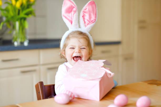 Niedliches kleines Kleinkind trägt Osterhasen-Ohren mit farbigen Pastelleiern. Glückliches Kind auspacken Geschenke. Entzückend gesund lächelndes Kind in rosa Kleidung genießen Familienurlaub – Foto