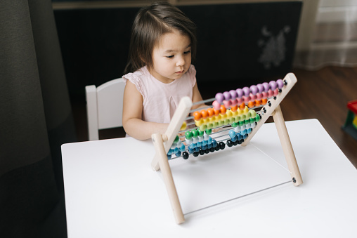 1019302738 istock photo Cute little two-year-old girl wearing white dress is playing with multicolored abacus. 1225836706