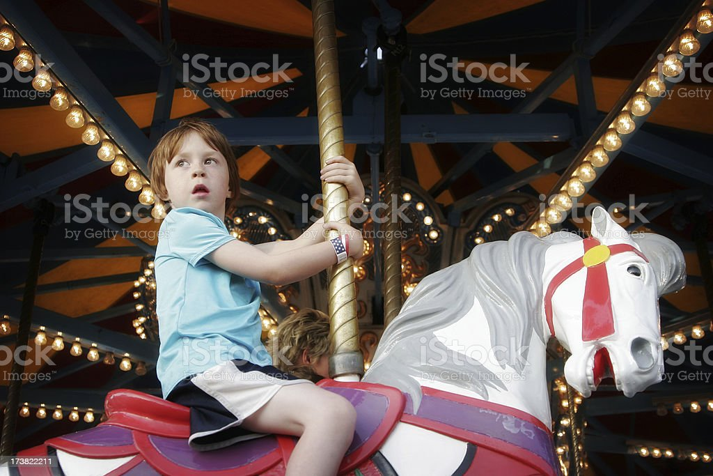Cute Lonely Child on Merry Go Round royalty-free stock photo